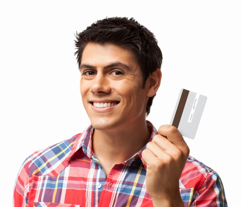 Portrait of young man smiling while holding credit card. Horizontal shot. Isolated on white.