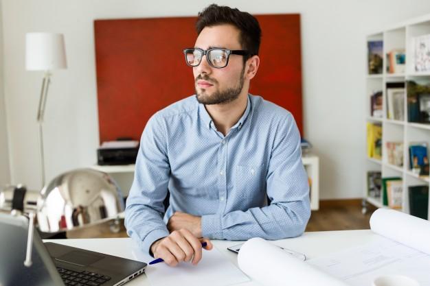 joven-trabajador-de-oficina-masculino-en-el-lugar-de-trabajo_1301-2824